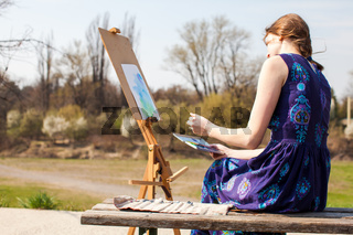 Young woman creative painter draws brush watercolor paints on canvas outdoors. Spring inspiration.