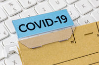 A brown file folder labeled with COVID-19