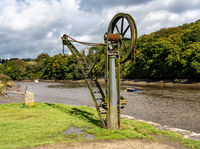 Old steel cargo winch on harbour by tidal River Tamar in Devon