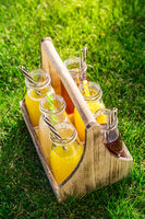 Assortment of lemonade and ice tea in bottles in wooden rack in the grass