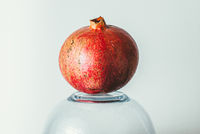 ripe red pomegranate on an inverted glass bowl. Healthy vegetarian food