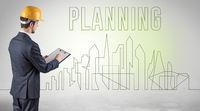 Businessman in hard hat holding blueprint
