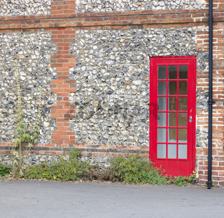 25 July 2020 - England, United Kingdom: Door of red telephone box built into wall