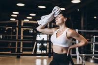 Smiling fit girl holding towel and taking rest in gym. Girl wipes sweat with a towel