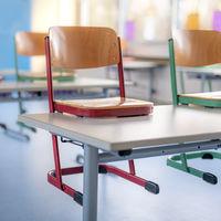 Roter Stuhl in einem Klassenzimmer steht auf einem Tisch vor unscharfem Hintergrund