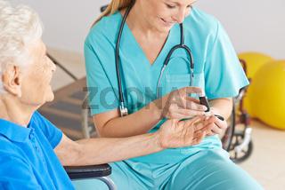 Altenpflegerin beim Messen vom Blutzucker