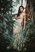 Gorgeous young woman wearing long evening fashionable dress posing in forest. Beauty and fashion concept