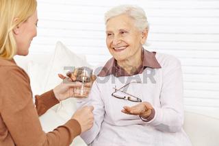 Seniorin nimmt Tablette mit Wasser ein
