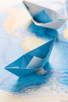 Small paper boats on world map. Concept of traveling or military exercise.