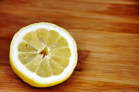lemon half sliced ​​on a wooden cutting board.