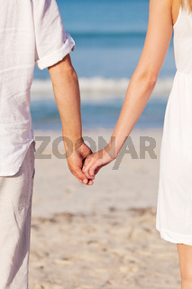 couple in love hand in hand on beach in summer