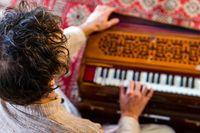 Shamanic playing kirtan music with harmonium