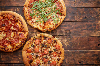 Composition of three various kinds pizzas on wooden table