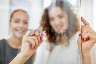 Business Frauen schreiben Ideen auf Glas