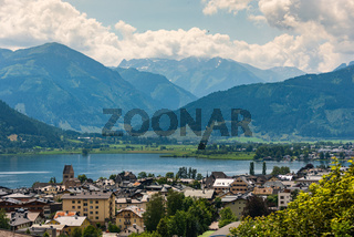 Cityscape of alpine city Zell am See with Zeller Lake in summer. Above view of Tirol lake, meadows and Tirol Alps Mountains in Austria.