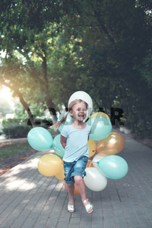 Happy little girl with bunch of colorful balloons running