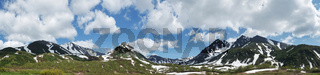 Beautiful spring mountain landscape, panoramic view of majestic mount peaks with clouds in blue sky