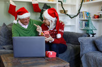 Senior couple in santa hat sitting on couch holding gift box and smiling looking at each other while