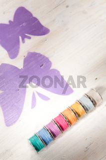 Colorful threads on a wooden box with painted butterflies