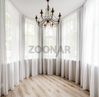 Elegant room interior with wooden floor, white curtain and chandelier