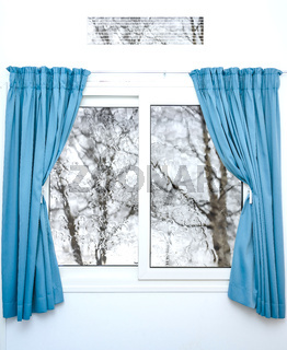 White window with blue curtains on a rainy day