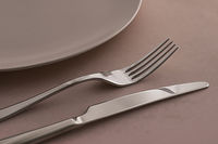 Empty plate and cutlery as mockup set on brown background, top tableware for chef table decor and menu branding