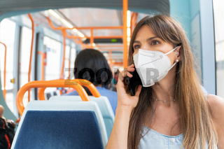 Woman wearing face mask talking on the phone onboard train