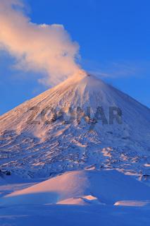 winter volcanic landscape of Kamchatka Peninsula: active Klyuchevskoy Volcano at sunrise