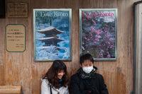Kyoto, Japan, Paar sitzt an einer Bushaltestelle vor Werbeplakaten  mit dem Slogan I Love Kyoto
