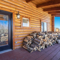 Square Log cabin with stacked firewood on the porch
