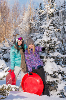 Two girlfriends in winter snowy forest bobsleigh