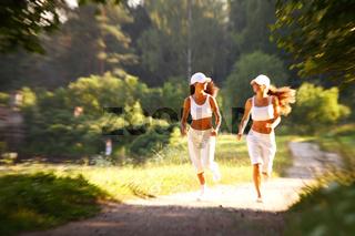 Two women run in park