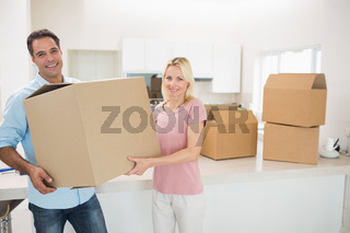 Smiling couple moving together in a new house