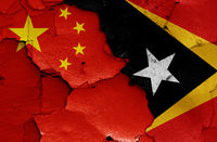 flags of China and East Timor painted on cracked wall