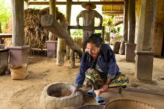 Einheimische Frau kontrolliert das Schälen der Reiskoerner, Ban Phong Van bei Luang Prabang, Laos