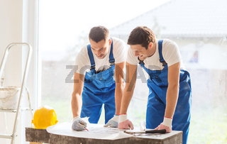 group of builders with blueprint