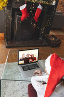 Rear view of woman in santa hat having a videocall with couple in santa hats waving on laptop at hom