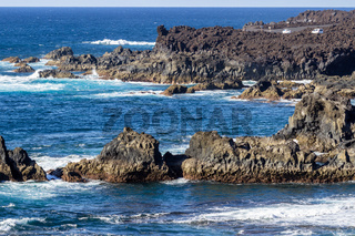 Rocky coastline Los Hervideros in the south west of canary island Lanzarote with rough sea, lava caves and multi colored volcanic rocks