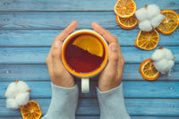 Hot warming tea with orange in female woman hand on blue wooden table