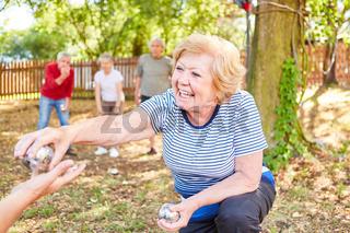 Seniorin spielt Boule im Garten im Sommer