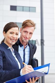 Zwei Berater mit Akten in der Stadt