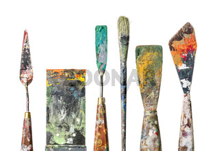 Various palette knives and a brush on a white background
