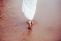 woman walking barefoot on sand beach