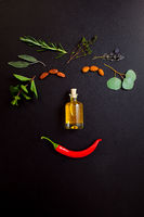 Smiling face making from herbs and bottle of essential oil on black background, top view, flat lay