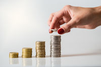 Woman holding silver coin in her fingers and putting it on top of growing column