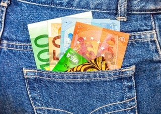 Euro banknotes and credit cards sticking out of the jeans pocket