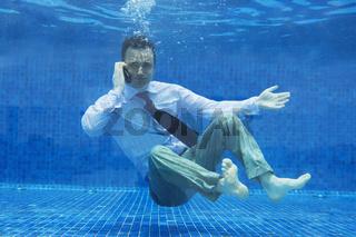 Businessman talking on phone underwater