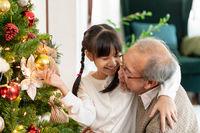 Girl and grandfather decorating a Christmas tree for season greeting.