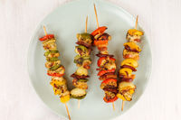 Chicken meat skewer and vegetables on white.