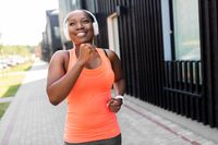 happy african woman in headphones running outdoors